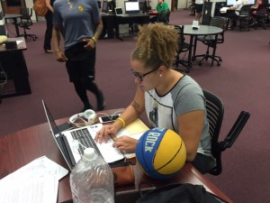 TCC basketball player Lindsay John studies with her ball by her side.